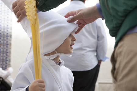 christianity palm sunday: ALMENDRALEJO, SPAIN, MARCH 29: placing the hat to young nazareno at Almendralejo Holy Week, Spain on March 29, 2015 Editorial