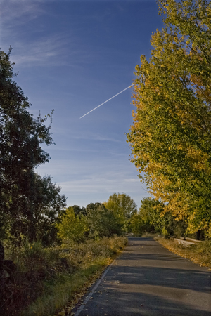opposed: Healthy little country road opposed to polluted jet trail in the sky, Caceres, Spain Stock Photo
