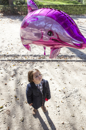 pink dolphin: Happy little girl holding a big balloon dolpin shaped in a park Stock Photo