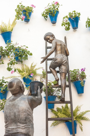 sculptural: Sculptural ensemble representing a granny and his grandson placing flowerpots on the wall Stock Photo