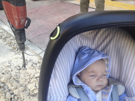 pounding head: Sleeping four month baby boy lying in strolller getting close dangerously to jackhammer on the street