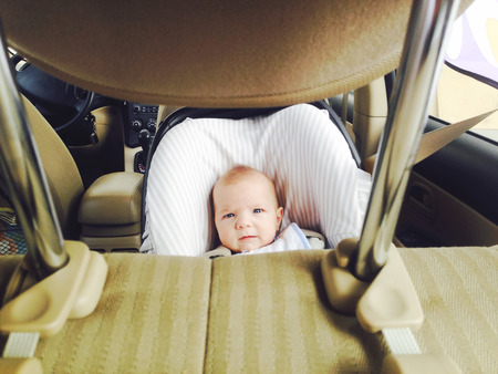 headrest: 4 months old baby boy in a safety car seat. Picture taken from headrest