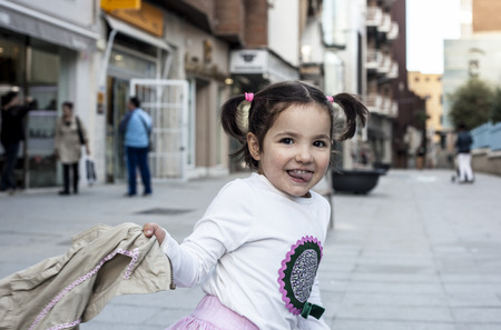 three year old: Happy three year old girl playing with her coat in the city. Selective focus