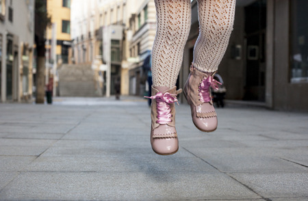three year old: Happy three year old girl jumping with pink satin lace boots on the city. Close up