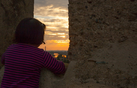 three year old: Three year old girl gazing at sunset from the Middle Age wall of Badajoz, Spain. Selective focus