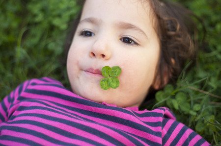 three year old: Happy three year old girl playing at grass meadow with clovers. Selective focus