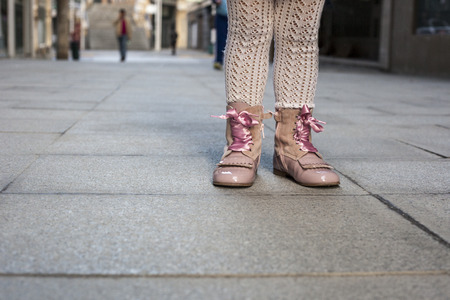 pink satin: Happy three year old girl wearing pink satin lace boots on the city. Close up Stock Photo