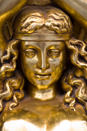 sconce: Golden bust head of a Greek maiden  flanking the entry of a classic building, Salamanca, Spain