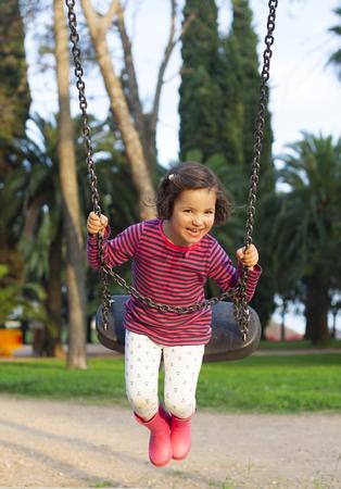 three year old: Happy three year old girl having fun on a swing