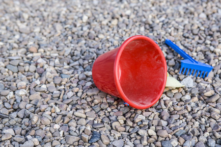 beach toys: Child stony playground with beach toys. Background with red bucket, blue rake and yellow shovel