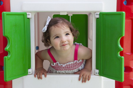 lean out: Little brown hair girl smiling through the window of kids playhouse