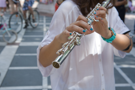 transverse: Young girl with blue snails playing transverse flute on the street