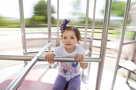 slow motion: Beautiful little girl on  metal human-powered caruosel. Slow motion shot