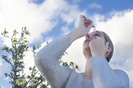 eyedropper: Young woman using eyedropper to treat irritated eyes at flowers meadow Stock Photo