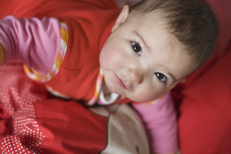 bed clothes: Little baby girl with beautiful dark eyes looking up just after awakening. Red bed clothes background Stock Photo
