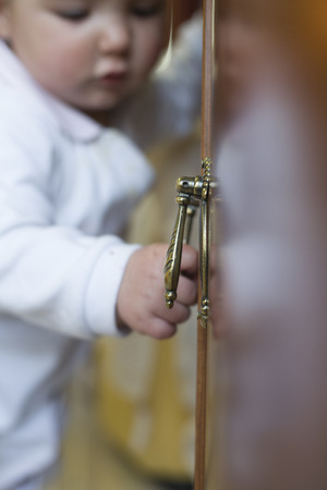 forniture: 9 month baby pulling a handle to open a forniture door of a living room. Selective focus Stock Photo