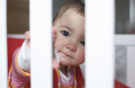 cot: Ten month baby girl playing hide-and-go-seek behind the bars white cot Stock Photo