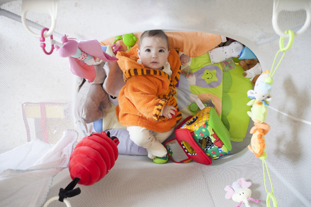 Cute baby girl at playpen full of soft toys. 8 months old