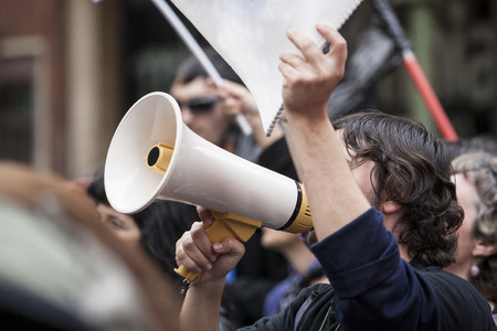 demonstrator: Unidentified young demostrator with megaphone and notebook protesting against austerity cuts