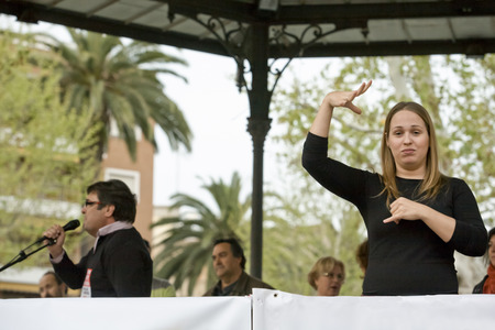 protests: Badajoz, Spain - March 29, 2012: sign language woman interpreter gestures during a meeting that protests against austerity cuts
