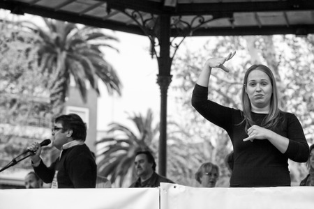 Badajoz, Spain - March 29, 2012: sign language woman interpreter gestures during a meeting that protests against austerity cuts Imagens - 55987602