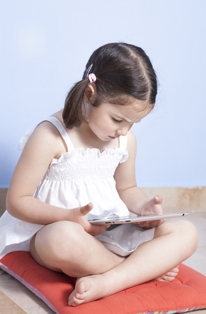 barefooted: Little girl sitting on  her room floor using tablet computer Stock Photo