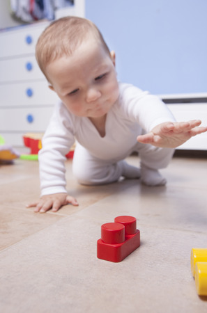 romper: 9 month baby boy playing with plastic building blocks. Selective focus