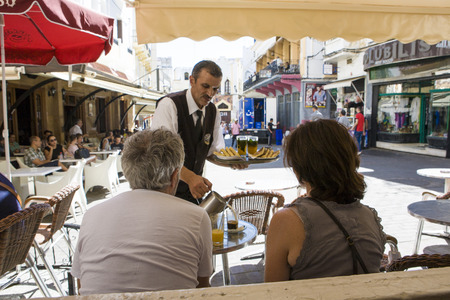 COSTUMERS: Tangier, Morocco - August 20, 2014: a waiter serves milk at Petit Souk Place for a mature couple