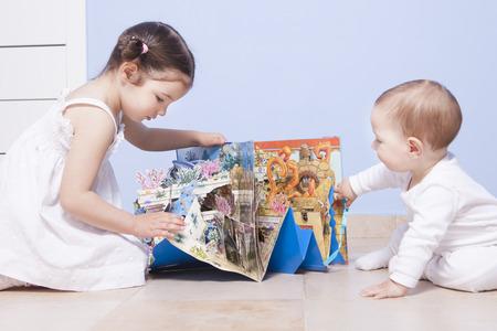 De jongen en de zuster van de baby spelen op speelgoed kamer met een pop-up boek Stockfoto