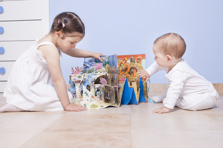 romper: Baby boy and sister playing at toys room with pop up book