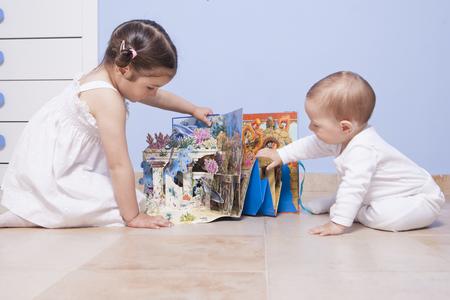Chłopiec i siostra gra na sali zabawek z pop up książki Zdjęcie Seryjne