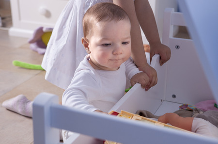 romper: Baby boy playing with his sister at toys room. They are taking out toys from their trunk