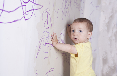 plasterboard: Baby boy drawing with wax crayon on plasterboard wall. He is looking to the camera