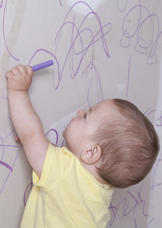 plasterboard: Baby boy drawing with wax crayon on plasterboard wall. He is reaching up high