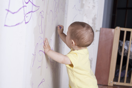 plasterboard: Baby boy drawing with wax crayon on plasterboard wall. We can see a wooden safety gate Stock Photo