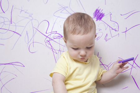 plasterboard: Baby boy drawing with wax crayon on plasterboard wall