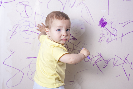 Baby boy drawing with wax crayon on plasterboard wall. He is looking to the camera Reklamní fotografie - 58973795