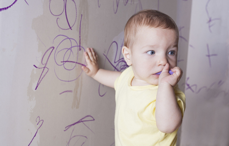 plasterboard: Baby boy drawing with wax crayon on plasterboard wall. He has the crayon on the mouth thinking what to do