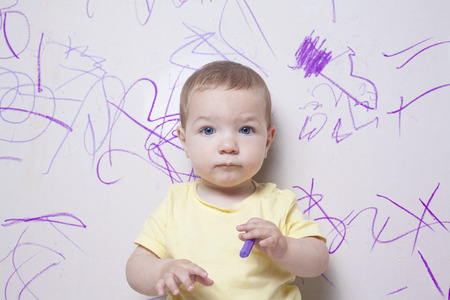 plasterboard: Baby boy with wax crayon on plasterboard wall. He is looking to the camera Stock Photo