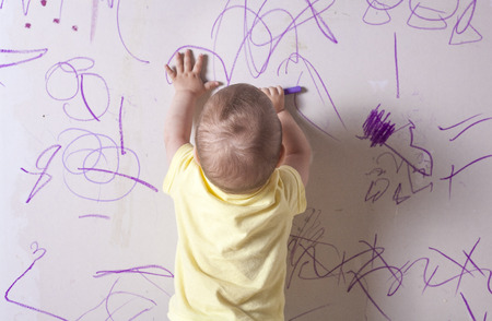 plasterboard: Baby boy drawing with wax crayon on plasterboard wall. He is with his back towards