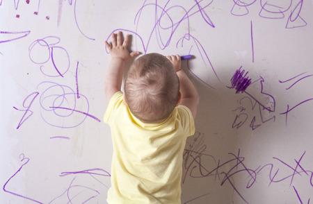 Baby jongen tekenen met waskrijt op gipsplaten muur. Hij is met zijn rug naar Stockfoto