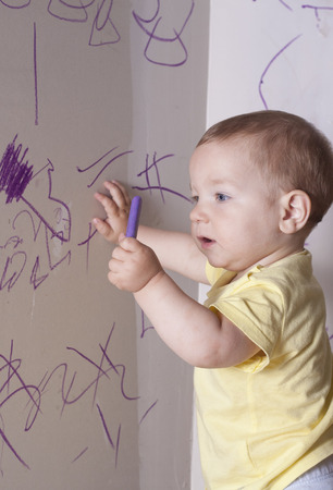 plasterboard: Baby boy drawing with wax crayon on plasterboard wall. He is looking to the crayon