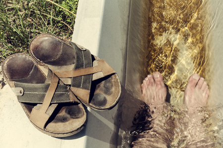 hottest: Man feet refreshing in a cool irrigation canal during the hottest day hours, Vegas Altas del Guadiana, Spain Stock Photo