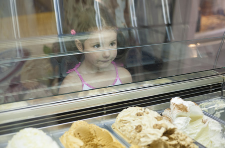 pastry shop: Little girl wishes ice cream in pastry shop. Reflections on ice cream counter glasses