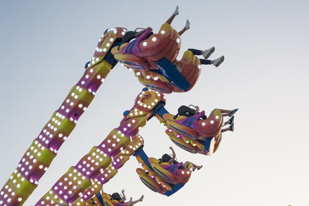 liberated: Hanging funfair attraction with people having fun. low angle view