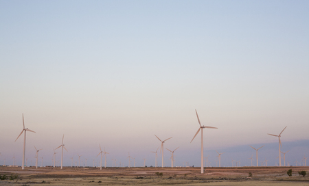 windy energy: Electric wind turbines farm with sunset light on arid landscape, Spain
