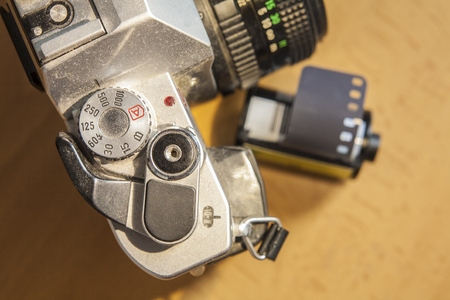 slr: Antique SLR or Reflex camera with film roll over wooden surface Stock Photo