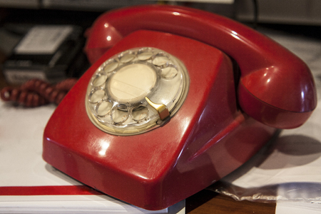 hangup: Old Fashioned Red phone over home desk full of papers Stock Photo