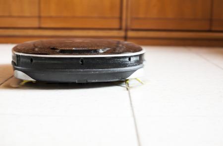 slow motion: Robotic vacuum cleaner on floor glazed tile at work. Slow motion shot