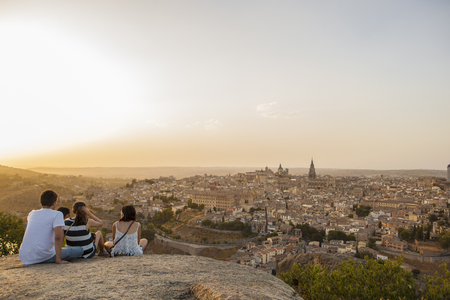 Toledo, Spain - July 27, 2016: Young people sitting on the stone enjoying peaceful magic moment of sunset over Toledo City, Spain